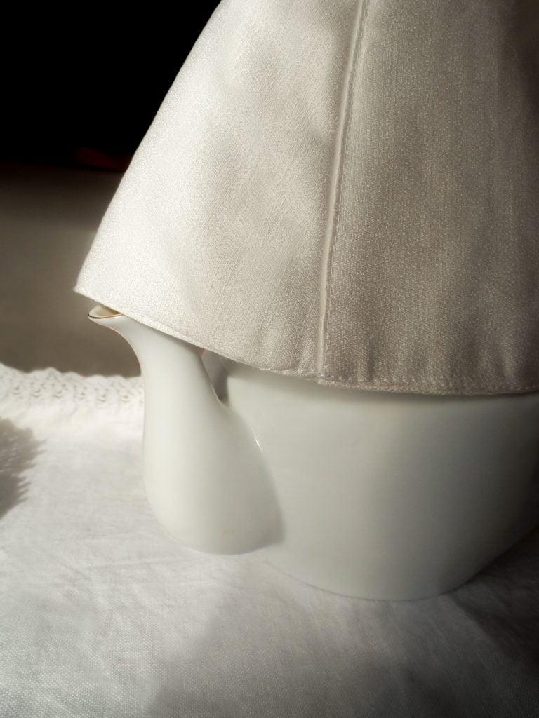 Copriteiera di stoffa con teiera bianca